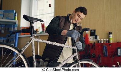 Focused mechanic is assembling bicycle placing handle-bar...