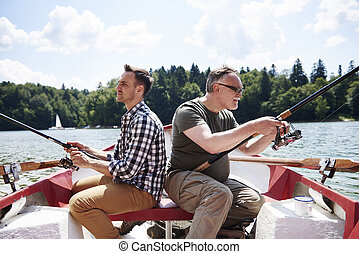 Focused men fishing on a rowboat