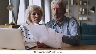Serious older couple managing family budget at home. - ...