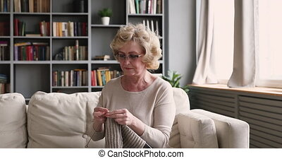 Focused middle aged retired woman knitting warm sweater.