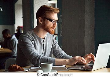 Focused millennial redhead man using laptop sitting at cafe tabl
