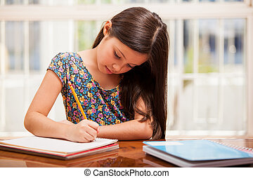 Beautiful little girl looking focused and concentrated on doing her homework
