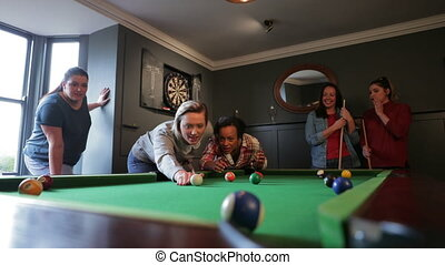 Small group of friends playing eight ball pool in the games room at home. A young female adult is lining up the cue-ball to take her shot.