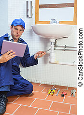 Focused plumber consulting tablet