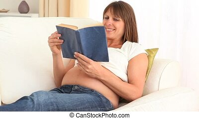 Focused pregnant woman reading