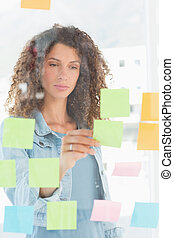 Focused pretty designer looking at sticky notes on window
