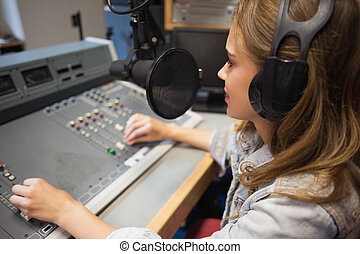 Focused pretty radio host moderating sitting in studio at...