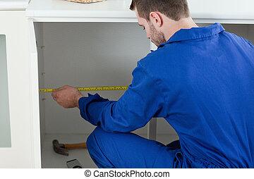 Focused repair man measuring something