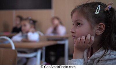Focused schoolgirl listening to teacher in lesson