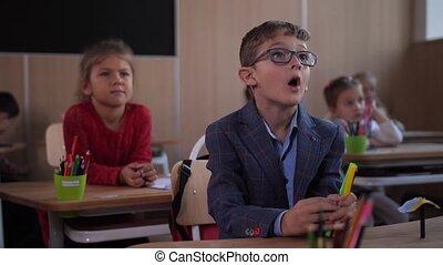 Focused schoolkids listening to teacher in class