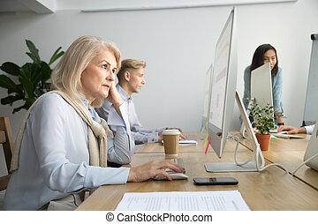 Focused senior businesswoman working on desktop sitting at offic