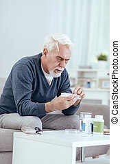 Focused senior man counting pills