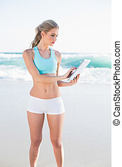 Focused slender blonde in sportswear using tablet