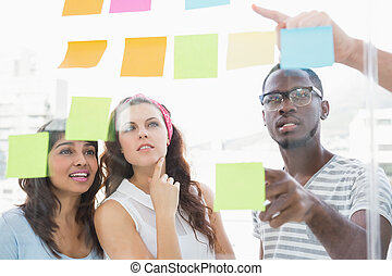 Focused teamwork reading sticky notes in the office