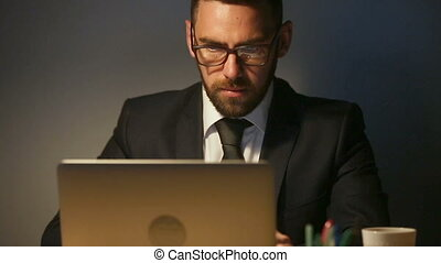 Focused thoughtful businessman working late on laptop, urgent deadline task