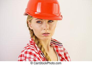 Focused woman wearing worker red helmet