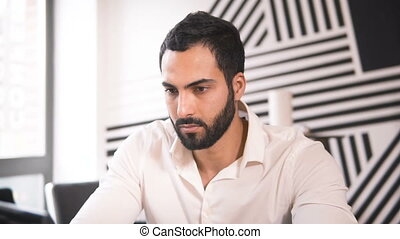 Focused Worker in Office - Serious bearded man doing the job...