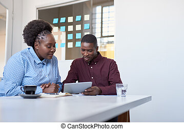 Focused young African colleagues using a tablet in a modern office