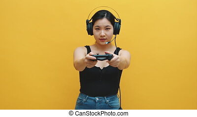 Focused young asian woman with headset and joystic controller playing video games. Isolated on yellow background. High quality 4k footage