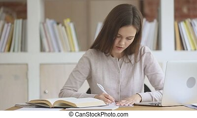 Focused young female teen student making notes in copybook.