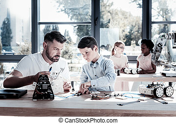 Focused youngster working on robot with his teacher