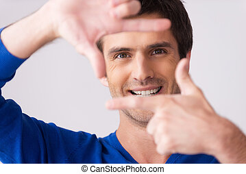 Focusing at you. Playful young man in blue sweater gesturing finger frame and smiling while standing against grey background