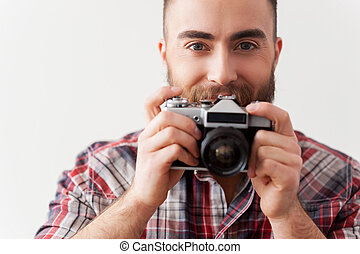 Focusing at you. Young beard man focusing at you with his retro camera while standing against grey background