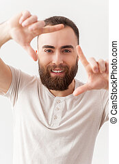 Focusing on you. Handsome young bearded man focusing on you and smiling while standing isolated on grey background