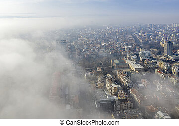 Fog clouds coming over the city from sea, aerial landscape from a drone. View from above.