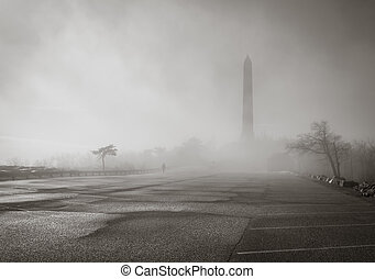 Fog envelops a park monument and barren trees in the winter