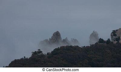 Fog hovering around the rocks. Timelapse