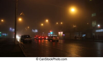 Fog in street of night city and cars on the road.