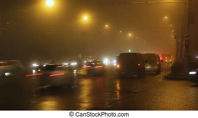 Fog in street of night city and cars on way.