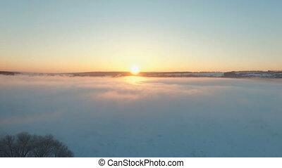 Fog in winter over the frozen river