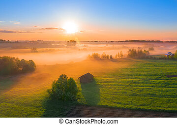 Fog morning over the plain and river floodplain of the meadow near a rural village with a house, aerial view landscape
