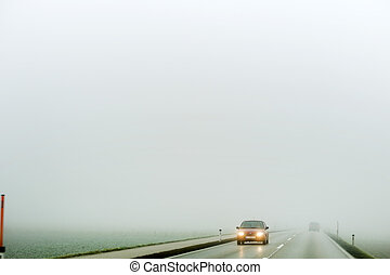 fog on a road with cars - car driving in the fog. poor ...