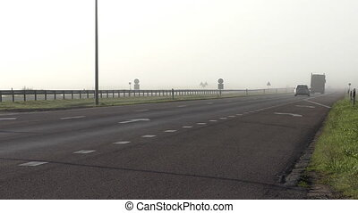 Fog on motorway - Car and lorry driving on motorway...