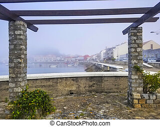 Fog on Xufre harbor and Arousa island seafront from a stone pergola on the boardwalk