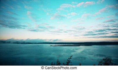 Fog over lake in the morning. Timelapse