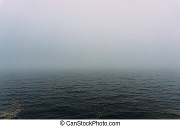 Fog over the water of the lake in autumn day