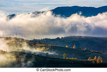 fog rising over the rural hills in morning light. dramatic...