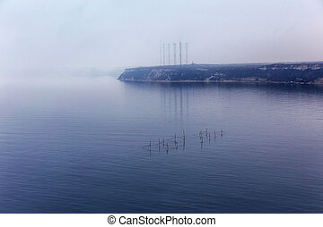 Fog. Seascape with fishing nets with the effect of film grain.