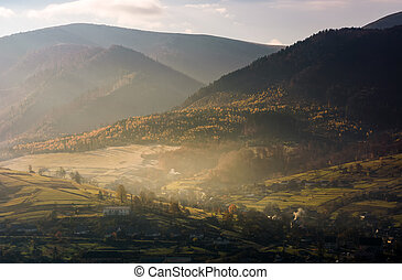 foggy autumn sunrise in mountainous rural area. village and...