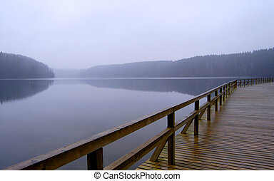 Lonely pier with rail on the foggy lake, tranquil late autumn scenery