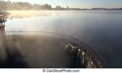 Foggy lake landscape with dam