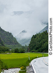 Foggy landscape with road in norwegian mountains