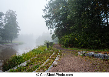 Foggy morning by the river with a path beside the treeline, Forssa Finland
