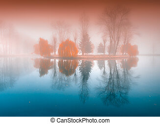 Foggy morning in autumn park on the lake