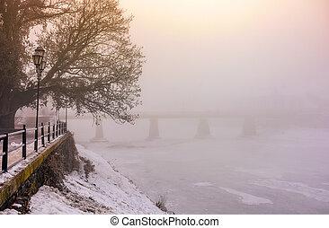 foggy morning near the bridge through the frozen river. tree...