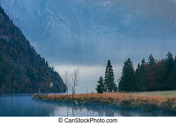 foggy morning on a lake in the mountains in a blue haze